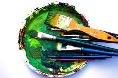 Paint brushes to the painting palette with colors on a white background - stock photo