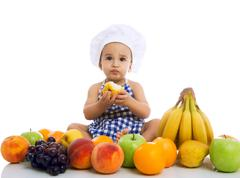 Sweet beautiful baby cook eating healthy fruits - stock photo