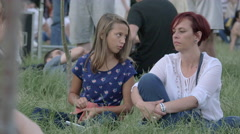 WMother and daughter sitting on grass at River Fest, Cluj-Napoca Stock Footage