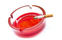 last cigarette on the edge of the red ashtray - stock photo