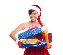 Christmas woman holding gifts wearing Santa hat.Iisolated on white background - stock photo