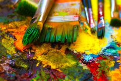 Paint brushes to the painting palette with colors Stock Photos