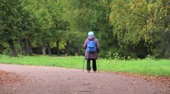 Old woman Nordic walking in the autumn Park Stock Footage