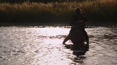 Pretty girl playing cello in the river Stock Footage