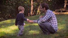 A father and cute toddler son spending time together outside in nature in slomo Stock Footage