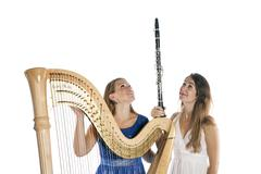 Two young women in studio with harp and clarinet against white background Stock Photos