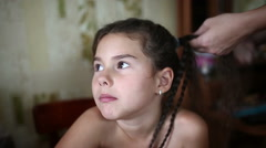 Mother makes daughter female girl hair braid  sitting in the morning Stock Footage