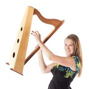 Young caucasian woman plays small harp in studio against white background Kuvituskuvat