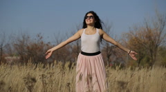 Woman with arms outstretched in a wheat field Stock Footage