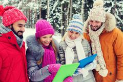 smiling friends with tablet pc in winter forest - stock photo
