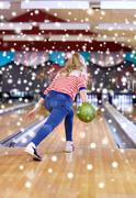 Happy young woman throwing ball in bowling club Stock Photos