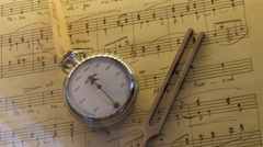 A clock and a metal on top of a music sheet Stock Footage