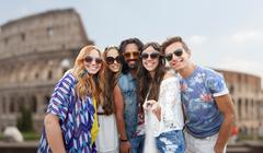 happy hippie friends with selfie stick at coliseum - stock photo