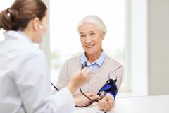 Doctor with tonometer and senior woman at hospital Stock Photos