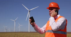 Engineer Wind Turbines Power Plant Tablet Supervise Mobile Phone Talk Teamwork - stock footage