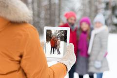 happy friends with tablet pc in winter forest - stock photo