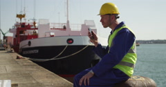 A dock worker standing at the harbor amidst shipping industry activity. Stock Footage