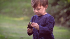 An innocent young child holding up something and asking what it is in slomo Stock Footage