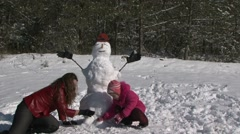 Mother of squatting alongside daughter and snowman and smile Stock Footage