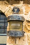 Vintage metal marine lantern attached to the wall of a stone building as adve Stock Photos