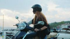 Young girl on scooter takes off her helmet and fixes her hair Stock Footage
