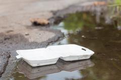 Styrofoam waste floating on riverbank, Object background of ecological harm. - stock photo