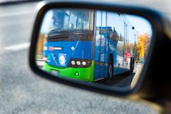 Bus visible in car's sideview mirror Stock Photos