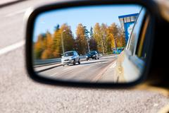 Traffic visible in car's sideview mirror - stock photo