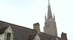 Bruges Cathedral tower over the roofs, zoom out Stock Footage