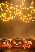 Illuminated carved halloween pumpkins lanterns - stock photo