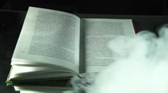 Old book in the mist on the black background Stock Footage