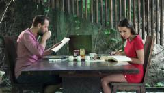 Young couple reading book and magazine during breakfast at home Stock Footage
