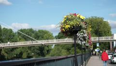 Stock Video Footage of 4K woman in red walks towards bridge with flowers by the river