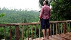 Young man walking out on terrace and admire view - stock footage