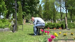 Stressed man shrink near mother lover grave in cemetery. 4K - stock footage