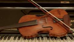Old violin lying on the piano. Stock Footage