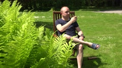 Alcoholic man drink beer sitting on wooden chair in middle of day. 4K Stock Footage