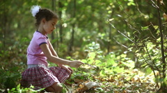 Teen girl sitting in a wild mushroom studies sunlight on a green background  Stock Footage