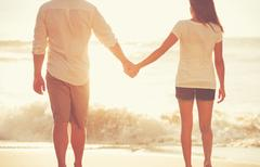 Young Couple Holding Hands on the Beach at Sunset - stock photo