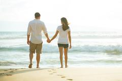 Couple Walking along the Ocean at Sunset - stock photo