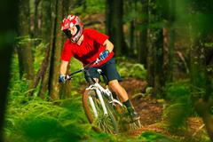 Mountain Biker Riding Down Forest Trail - stock photo