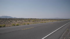 Vehicle Drives Along A Road in the Desert Stock Footage