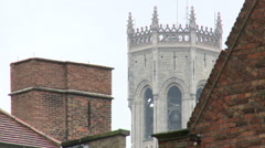 Belfry of Bruges behind chimneys in city centre Stock Footage