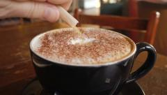 Adding sugar to cappuccino, slow motion Stock Footage