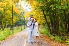Stock Photo of Young family for a walk in the autumn park with baby