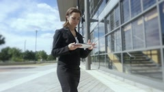Young businesswoman walking working tablet pc outside Slow motion Stock Footage