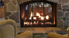 Woman sits puts feet up to fireplace at a luxury ski resort hotel - stock footage