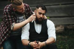 barber shaves a bearded man - stock photo