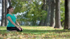 Beautiful young model woman practicing yoga in the Park,early autumn,Sunny day Stock Footage