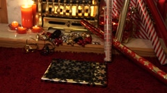 Caucasian hands wrap ribbons around christmas present in front of fireplace Stock Footage